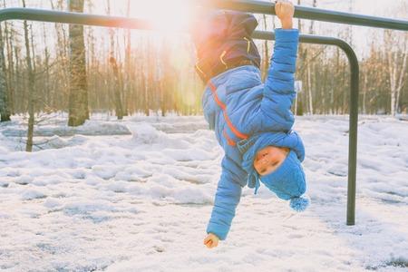 little boy playing on monkey bars in winter