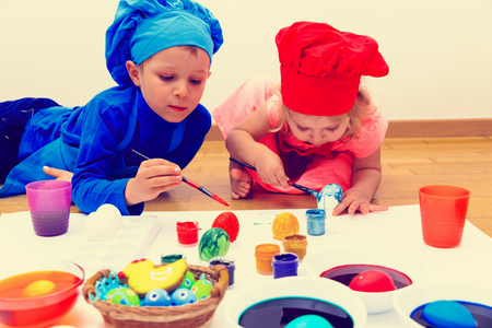 little boy and girl painting eggs for easter Stock Photo
