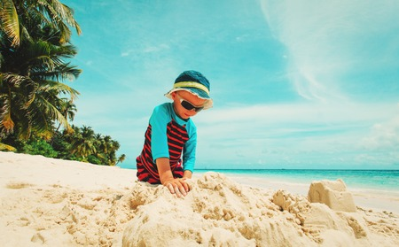 little boy play with sand on tropical beach Stock Photo