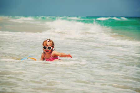 ittle: ittle girl play with water at beach Stock Photo