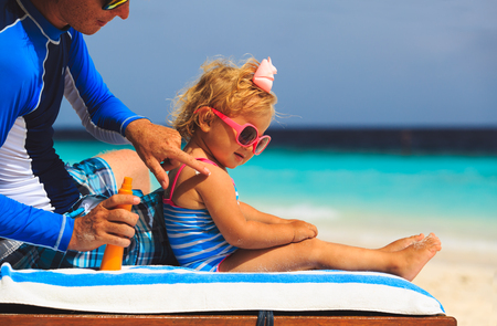 father applying sunblock cream on daughters shoulder