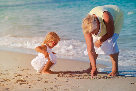 grandmother with little granddaughter play at beach