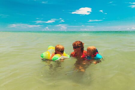 armbands: mother with son and daughter swimming at sea