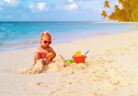 little girl play with sand on tropical beach