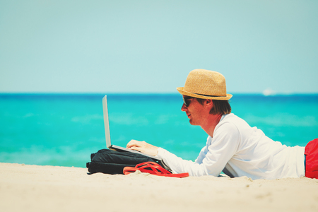 remote work concept -man with laptop on beach Stock Photo