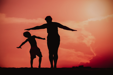 Silhouette of family play at sunset sky Stok Fotoğraf