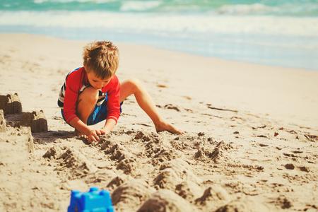 Kleine jongen spelen met zand op zomer strand Stockfoto