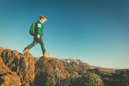little boy with backpack hiking in mountains
