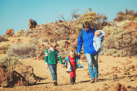 father with three kids travel hiking in mountains