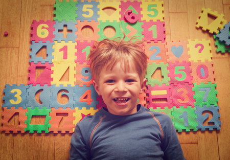 happy little boy playing with puzzle, education Stock Photo