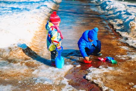 Kleine jongen en meisje in de lente met papieren boten plakken Stockfoto