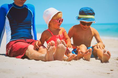 Vader met zoon en dochtervoeten op zandstrand