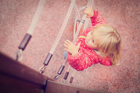 little girl playing on monkey bars at playground