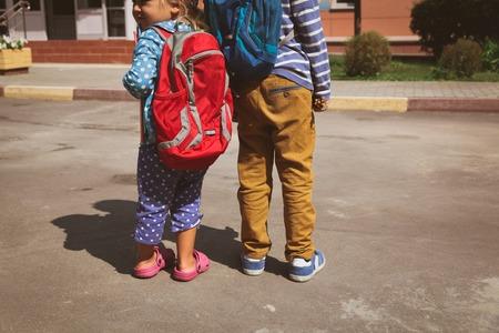 cognicion: los niños van a la escuela, pequeño niño y niña con mochilas Foto de archivo
