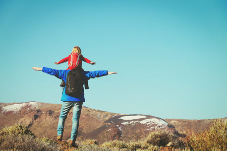 father with little daughter hiking in mountains
