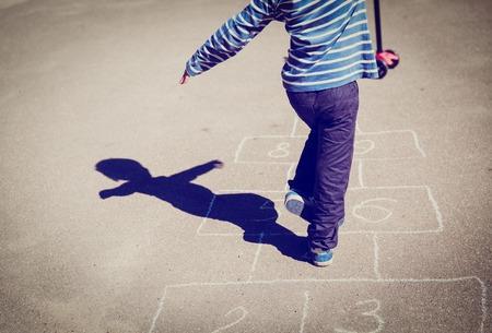 little boy playing hopscotch outdoors Stock Photo
