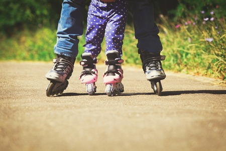 father teaching little daugther to roller skate