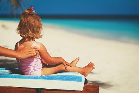 Zonbescherming -meer toepassen sunblock cream op kind schouder