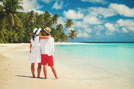 sunhat: happy loving couple walking on beach Stock Photo