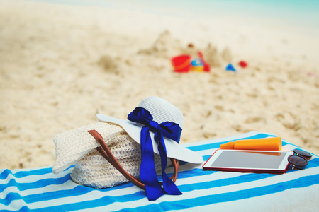 bag, suncream, glasses and touch pad on beach Stock Photo