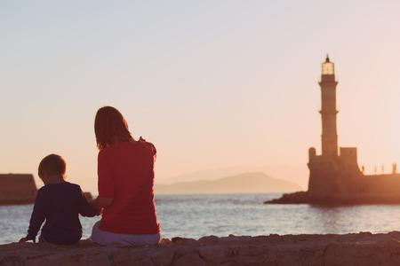 ギリシャの灯台で夕日を見て家族 写真素材