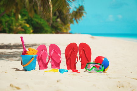Colored slippers, toys and diving mask at beach Stock Photo