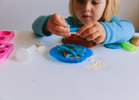 little girl playing with clay molding shapes Banco de Imagens