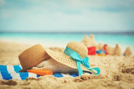 hats, bag, suncream and glasses on beach Stock Photo