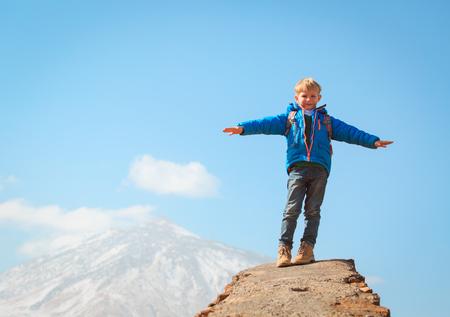 little boy hiking climbing in mountains