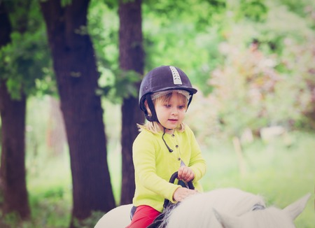 klein meisje paardrijden paard in de natuur Stockfoto