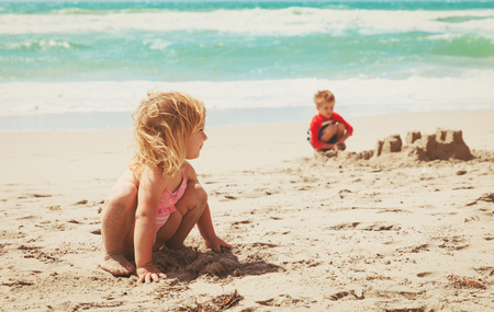 little girl and boy play with sand on beach Фото со стока