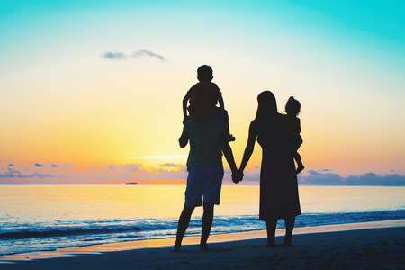 happy family with two kids walking at sunset Stock Photo
