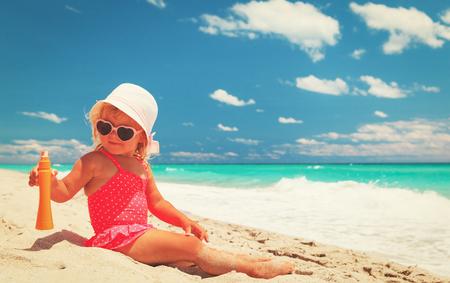 sunburnt: sun protection - little girl with suncream at beach