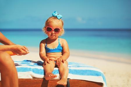 sun protection- mother applying sunblock cream on daughter Reklamní fotografie