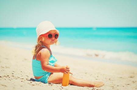 sun protection - little girl with suncream at beach