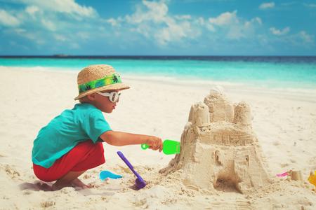 jongetje zandkasteel bouwen op het strand Stockfoto