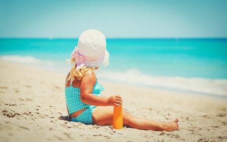 sunburnt: little girl applying sunblock cream on shoulder
