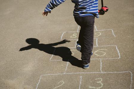 Petit garçon jouant à la marelle sur terrain de jeu Banque d'images - 83383399