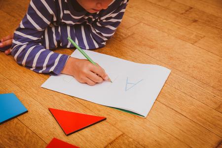 kleine jongen leren om brieven te schrijven