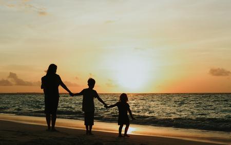 夕暮れ時のビーチで歩く 3 人の子供を持つ母