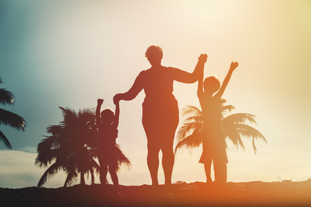 silhouette of family with kids play at sunset beach Stock Photo