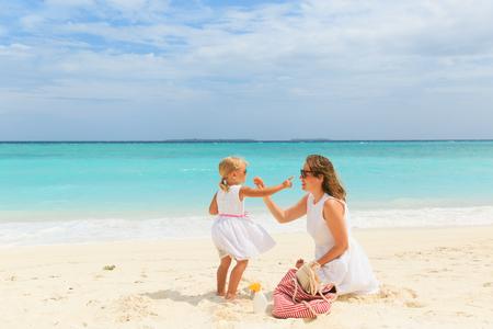 mother and daugghter applying sunblock cream on beach Stock Photo