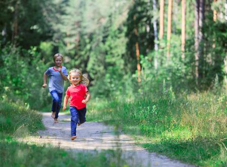 Gelukkig meisje en jongen rennen spelen in de zomer natuur