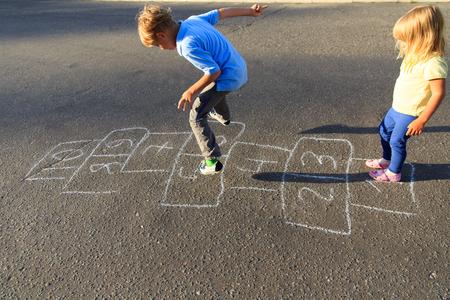 石けり遊びを遊び場で遊ぶ子供たち 写真素材 - 84147018