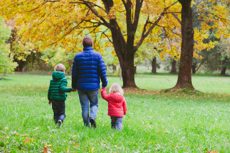 father with little son and daughter walk in autumn