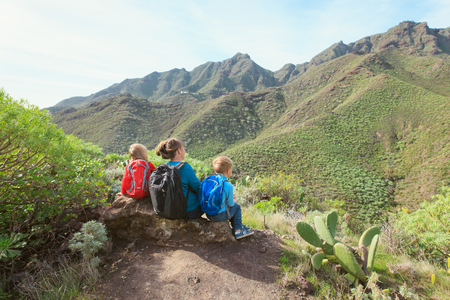 mother with two kids hiking in mountains