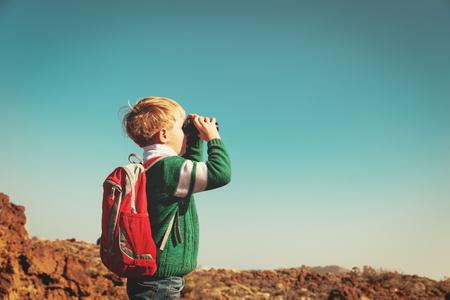 little boy looking through binocular hiking in mountains
