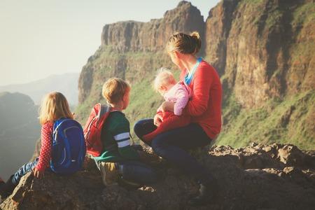 3人の子供が山をハイキングする母親
