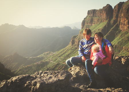happy couple with small baby travel in mountains