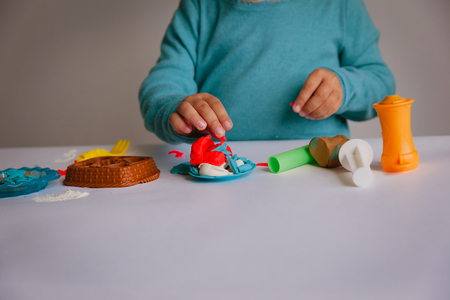 Child playing with clay molding shapes Stock fotó